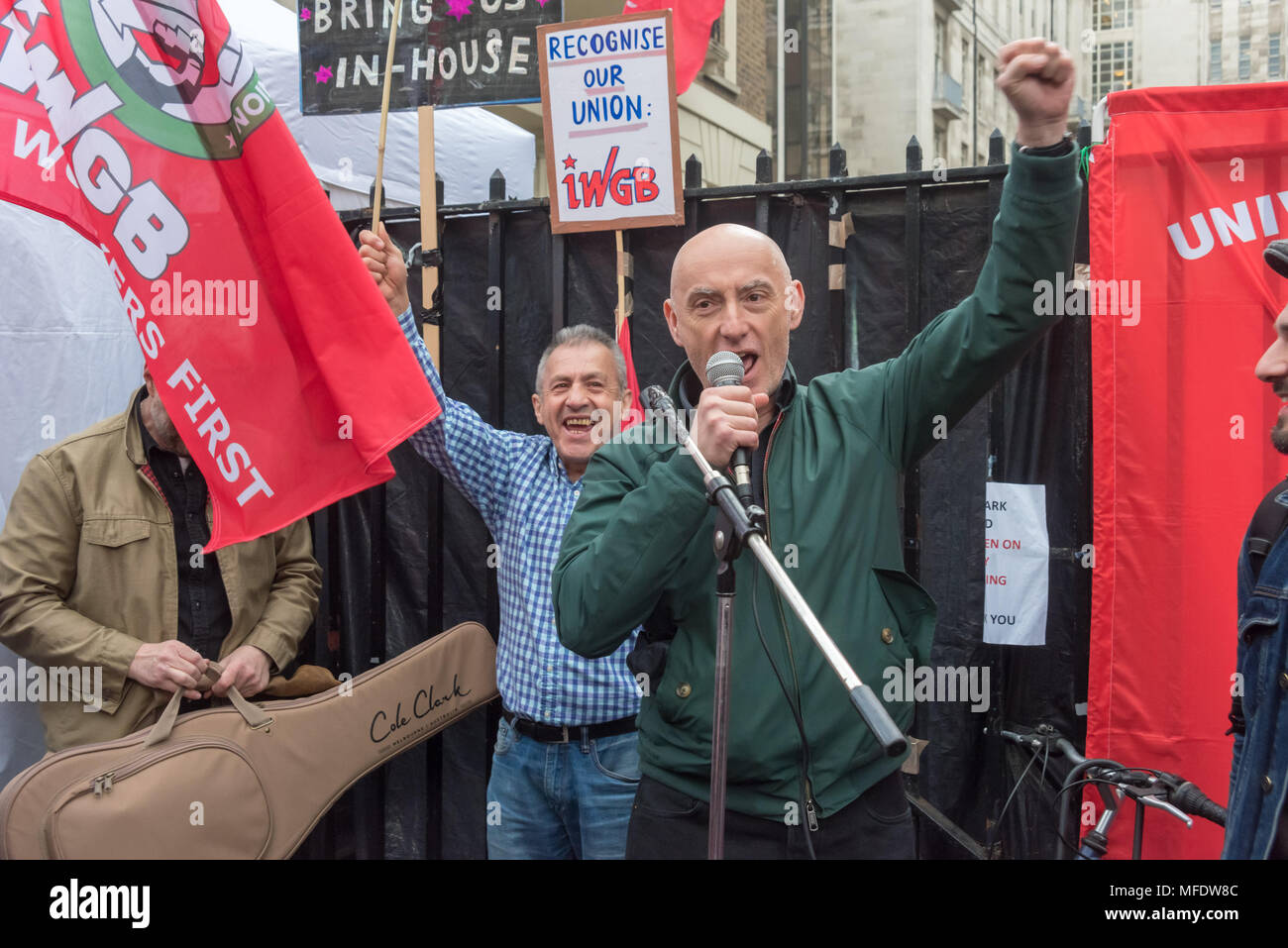 London, UK. 25th April 2018.Grim Chip of Poetry on the Picket Line raises his fist before he performs at the rally by workers, students and other trade unionists supporting over 100 cleaners, porters, security officers, receptionists, gardeners, post room staff and audiovisual staff in the Independent Workers Union of Great Britain - IWGB at the end of the first day of a two day strike at the University of London central administration. The workers, employed by various outsourcing companies are demanding to be directly employed by the University, and receive the same conditions and benefits as - Stock Image
