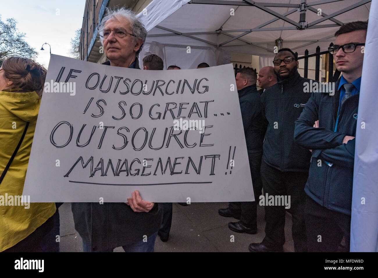 London, UK. 25th April 2018. A man holds a poster 'If Outsourcing is so great... Outsource Management!!' at the rally by workers, students and other trade unionists supporting over 100 cleaners, porters, security officers, receptionists, gardeners, post room staff and audiovisual staff in the Independent Workers Union of Great Britain - IWGB at the end of the first day of a two day strike at the University of London central administration. The workers, employed by various outsourcing companies are demanding to be directly employed by the University, and receive the same conditions and benefits - Stock Image