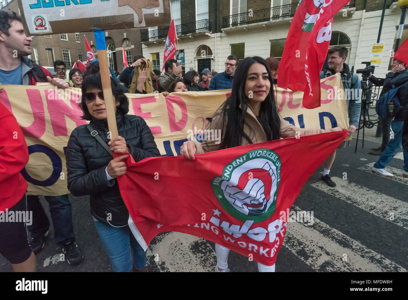 London, UK. 25th April 2018. People carry IWGB and UVW banners on the march from the rally by workers, students and other trade unionists supporting over 100 cleaners, porters, security officers, receptionists, gardeners, post room staff and audiovisual staff in the Independent Workers Union of Great Britain - IWGB at the end of the first day of a two day strike at the University of London central administration. The workers, employed by various outsourcing companies are demanding to be directly employed by the University, and receive the same conditions and benefits as directly employed colle - Stock Image