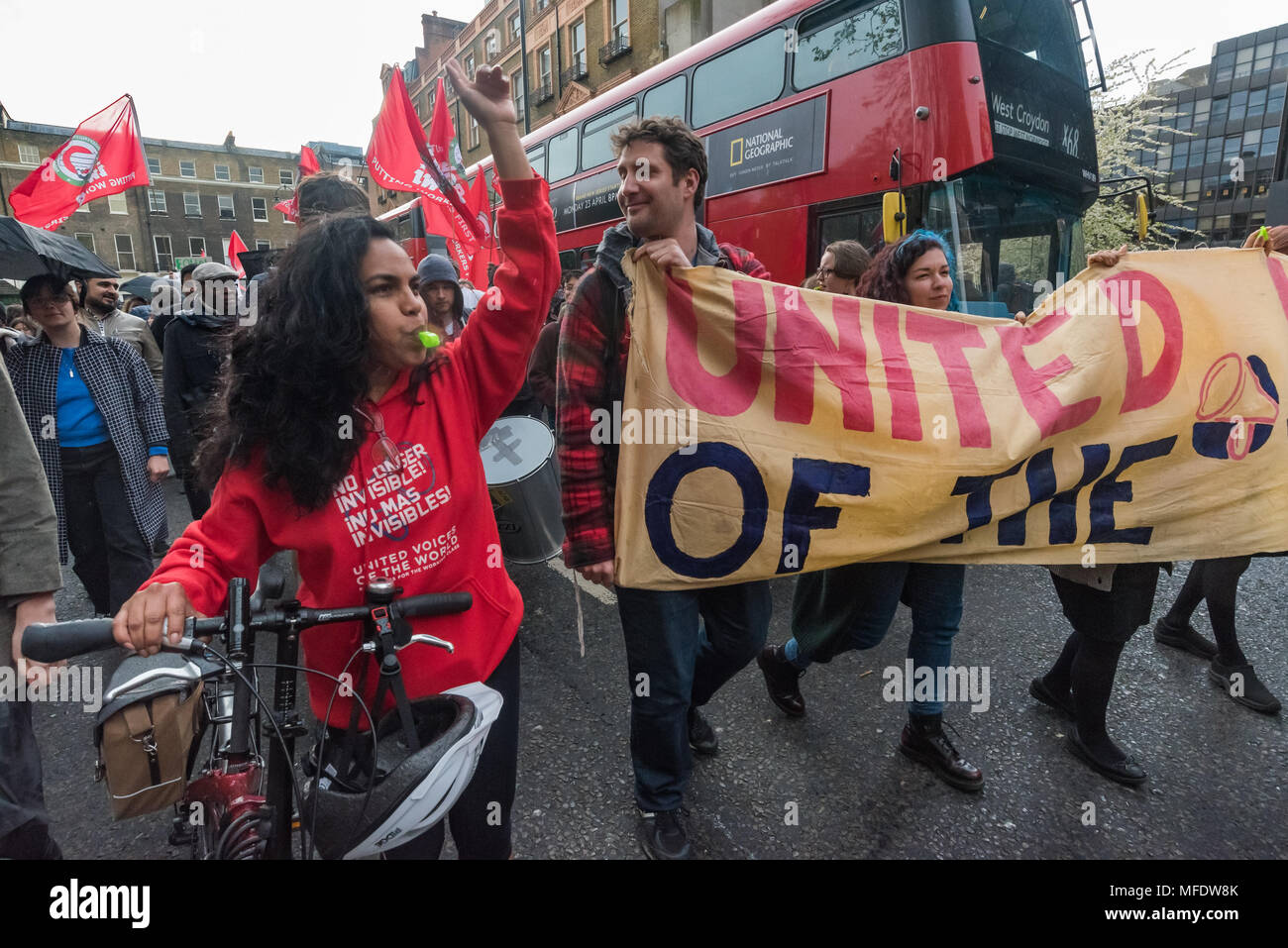 London, UK. 25th April 2018. People carry the  UVW banner on the march from the rally by workers, students and other trade unionists supporting over 100 cleaners, porters, security officers, receptionists, gardeners, post room staff and audiovisual staff in the Independent Workers Union of Great Britain - IWGB at the end of the first day of a two day strike at the University of London central administration. The workers, employed by various outsourcing companies are demanding to be directly employed by the University, and receive the same conditions and benefits as directly employed colleagues - Stock Image