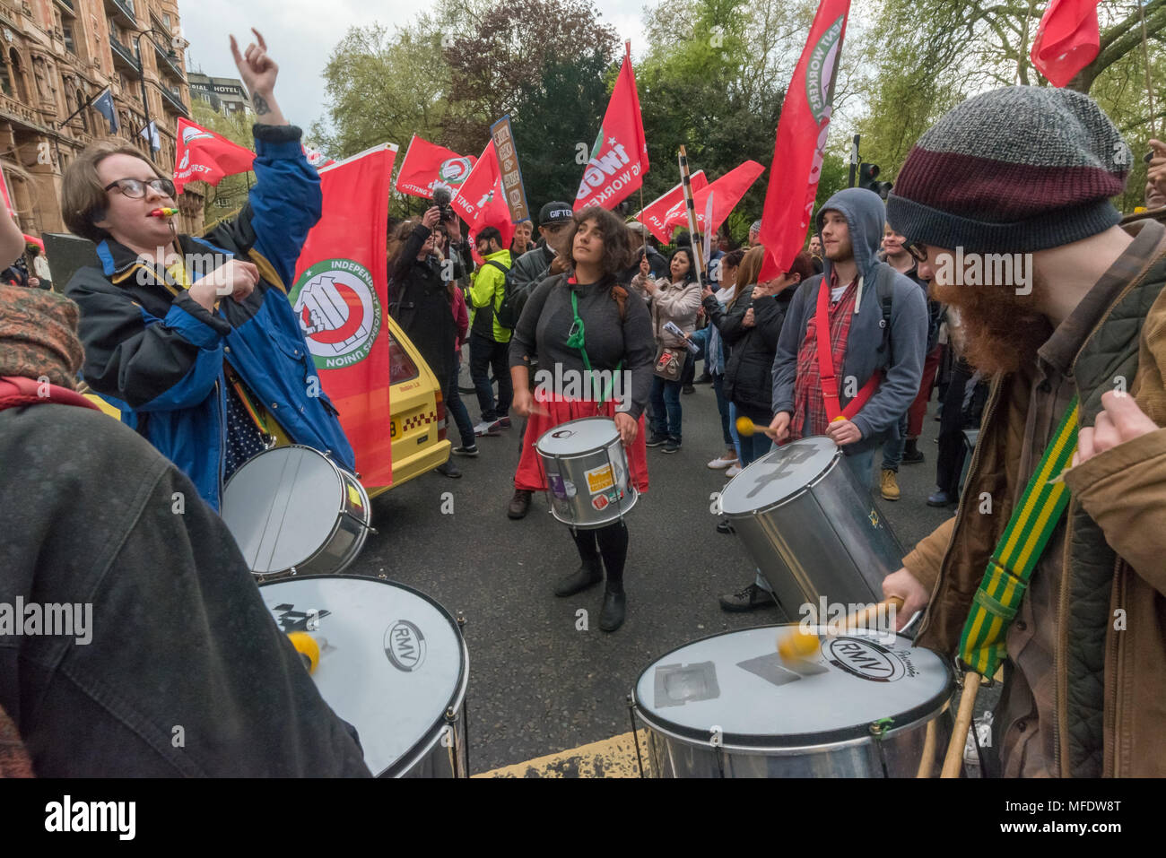 London, UK. 25th April 2018. Marchers briefly block the street on their march from the rally  by workers, students and other trade unionists supporting over 100 cleaners, porters, security officers, receptionists, gardeners, post room staff and audiovisual staff in the Independent Workers Union of Great Britain - IWGB at the end of the first day of a two day strike at the University of London central administration. The workers, employed by various outsourcing companies are demanding to be directly employed by the University, and receive the same conditions and benefits as directly employed co - Stock Image