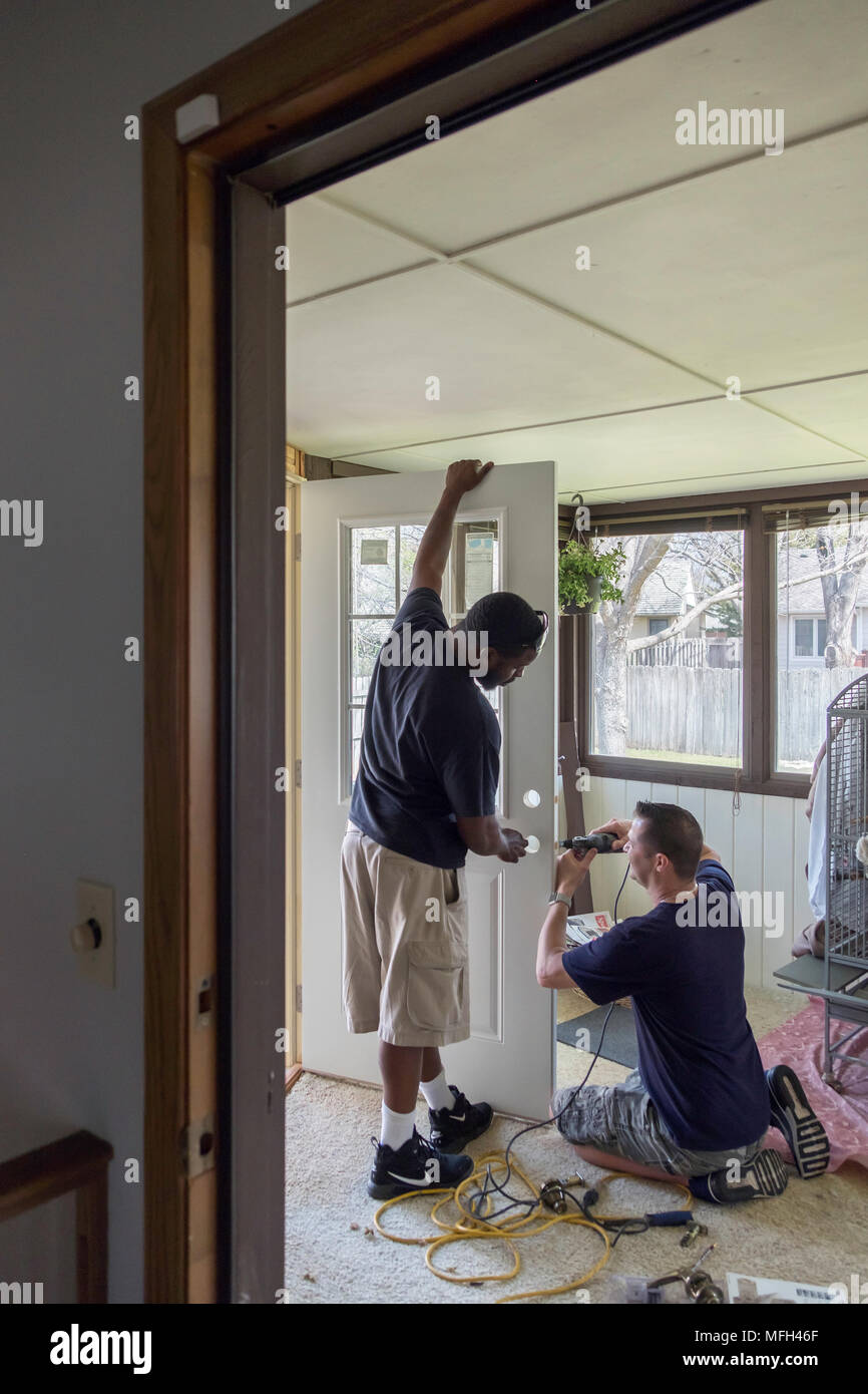 Two Men African American And Caucasian Work Together To Install An