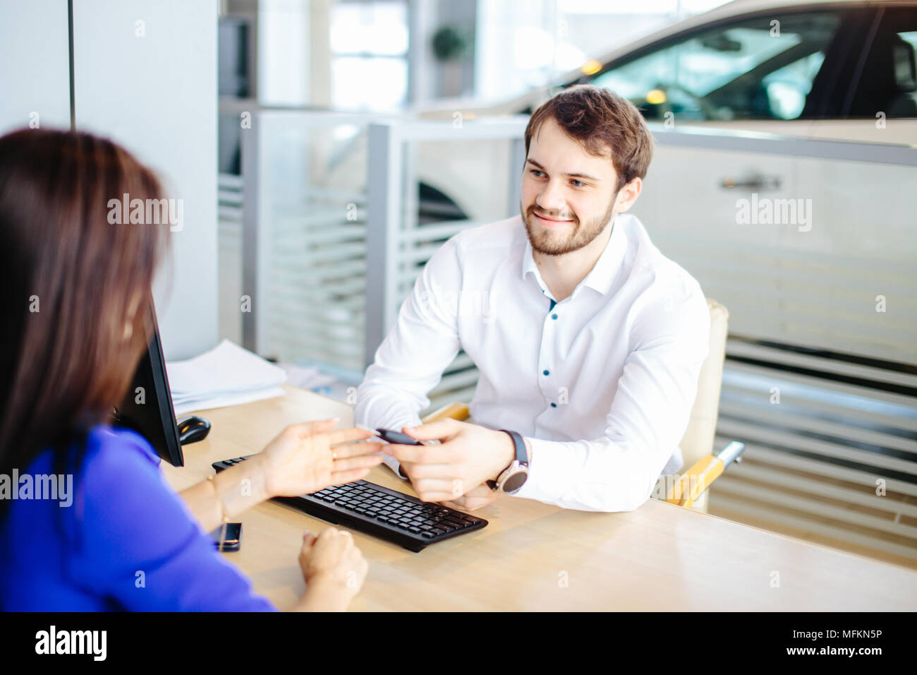 Handsome smiling salesman passing the keys to a purchaser woman after signing a contract - Stock Image