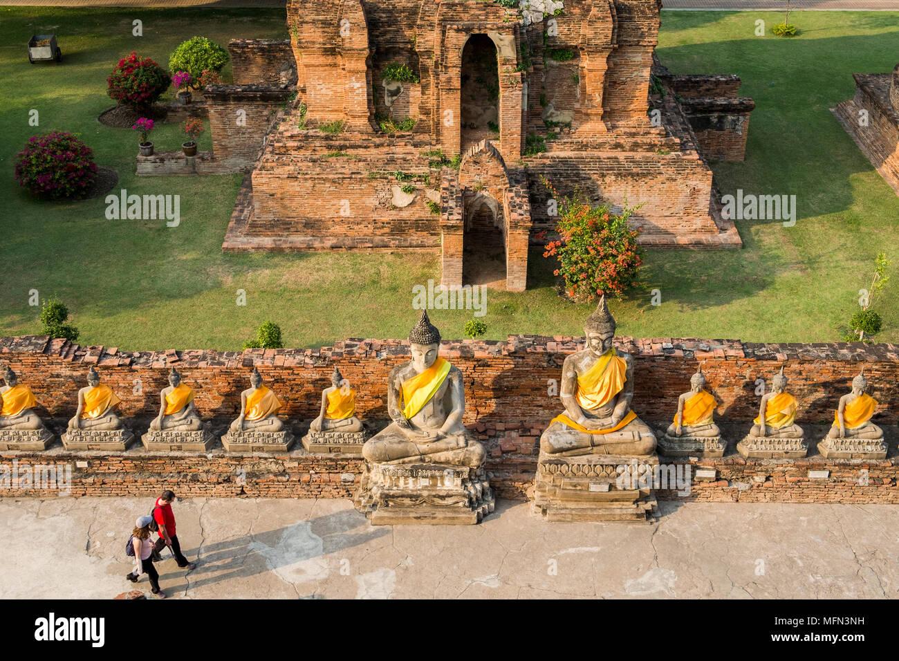 Two visitors walk past a row of Buddha statues at Wat Yai Chai Mongkhon, a 14th century Buddhist temple, Ayutthaya, Thailand. - Stock Image