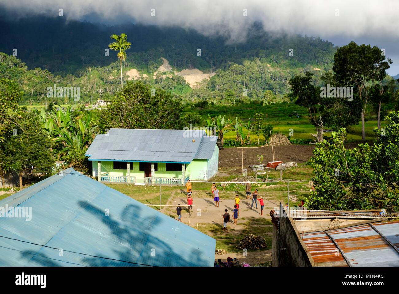 A group of kids and youngsters play a game of voleyball in the small village of Moni, Ende Regency, Flores Island, Indonesia. - Stock Image