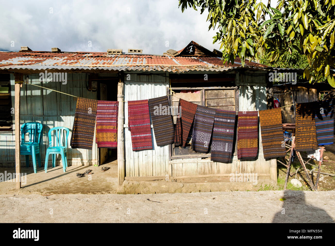 Pieces of ikat (a traditional weaving technique widely found in Indonesia) hanging on a rope in front of a house in Moni, Flores Island (East Nusa Ten - Stock Image