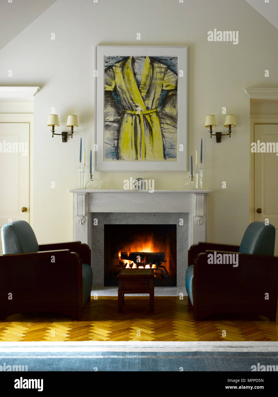 Two art deco style armchairs either side of lit fire in marble ...