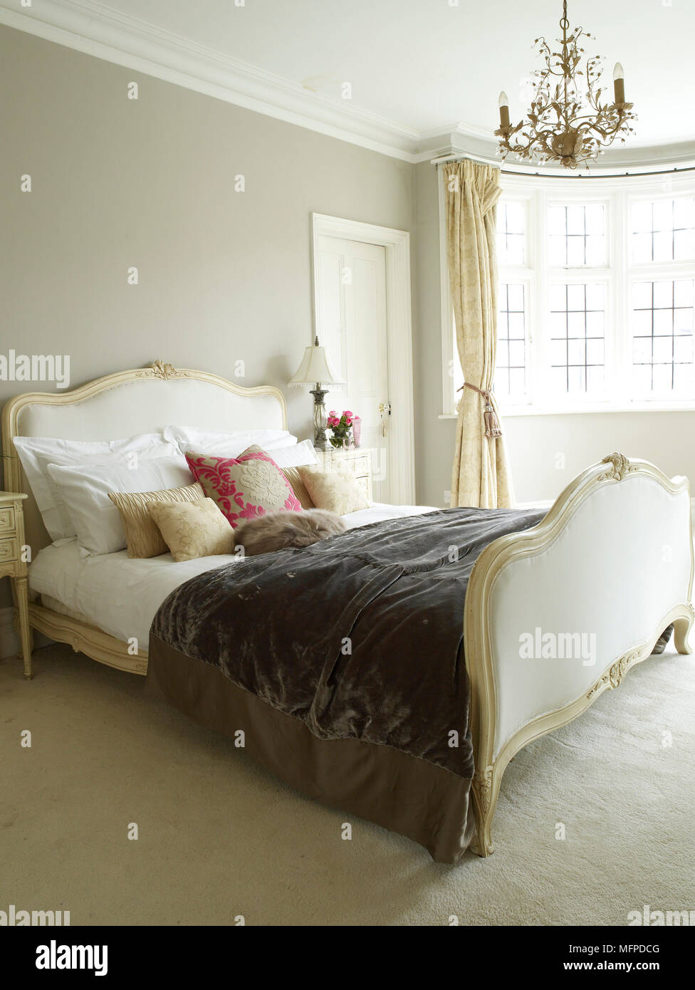Chandelier above period style double bed with upholstered head and footboard