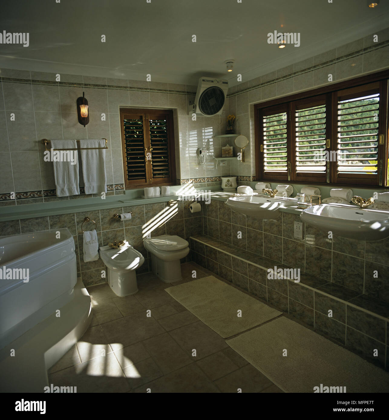 A modern tiled bathroom with a large jacuzzi bath next to a toilet ...
