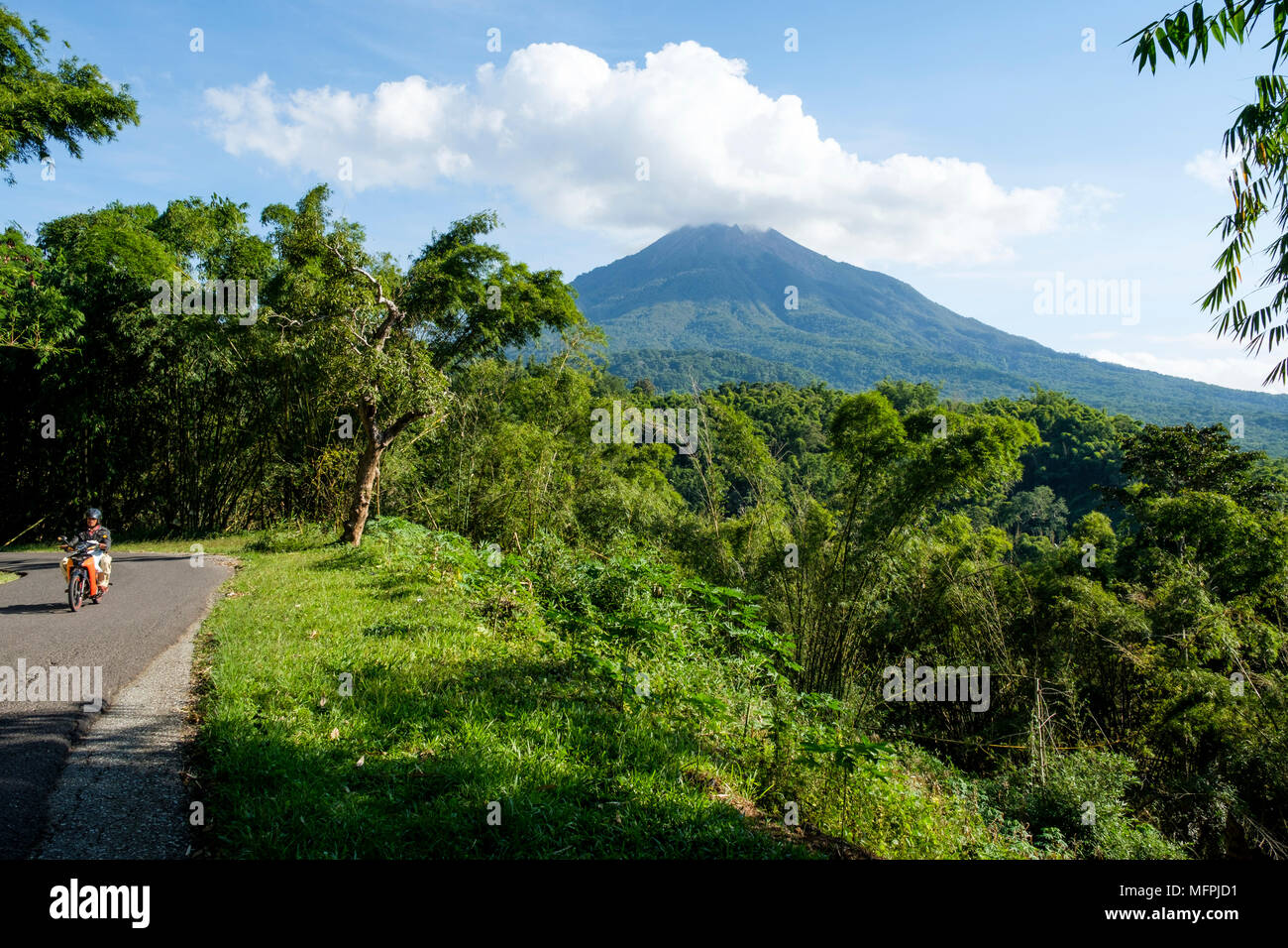 A man rides a motorbike on the road between Nangaroro to Bajawa, with Ebulobo stratovolcano in background, Island of Flores, Indonesia. - Stock Image