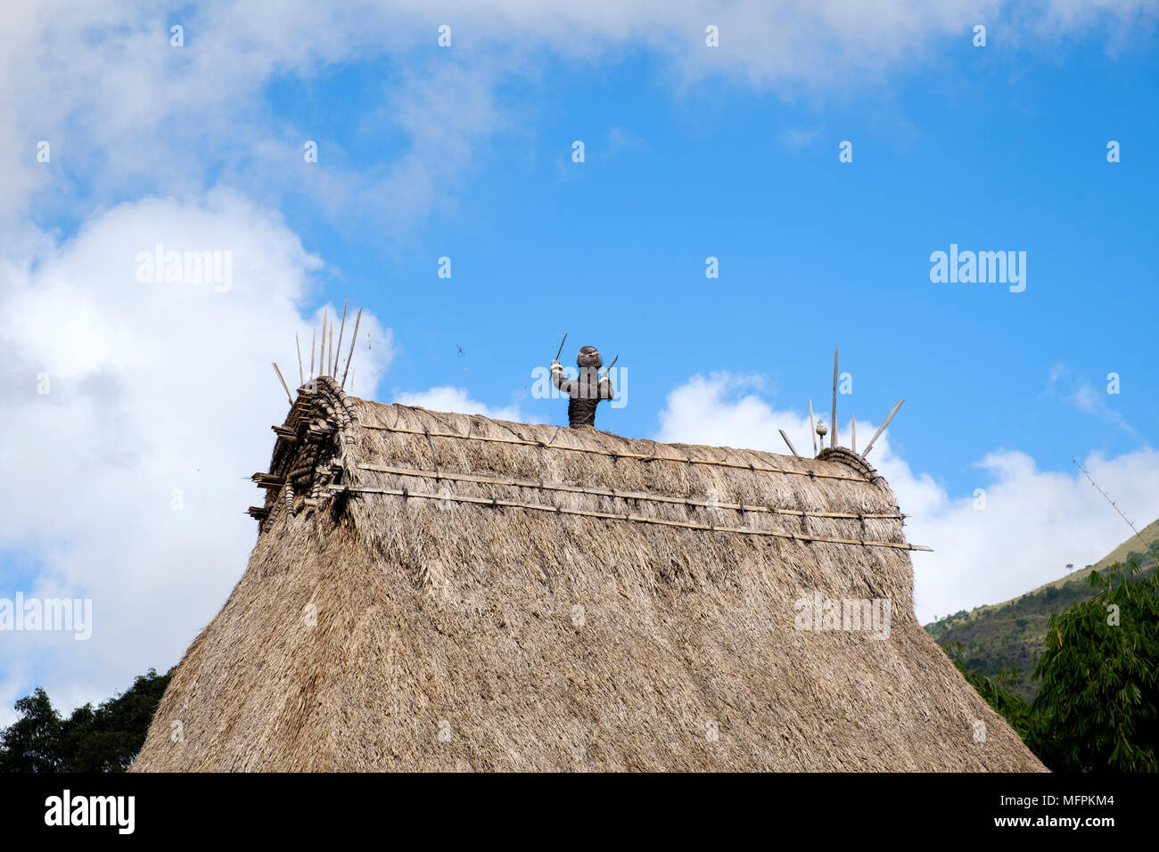 Traditional thatched roof with figures representing ancestors in Bena village, Ngada District, Flores Island (East Nusa Tenggara), Indonesia. - Stock Image