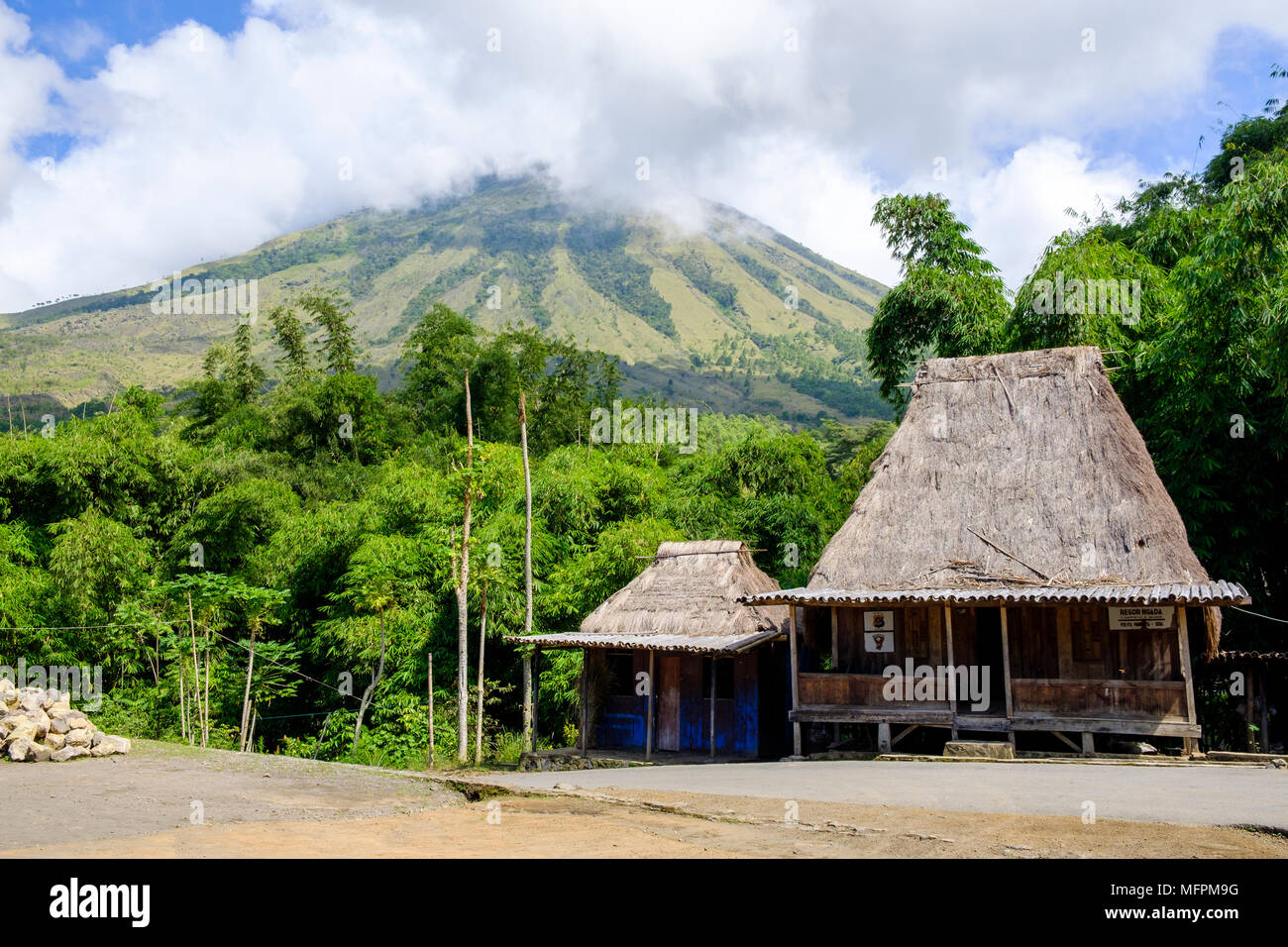 Inerie volcano looms behind two houses at Bena traditional village, Ngada District, Flores Island (East Nusa Tenggara), Indonesia. - Stock Image