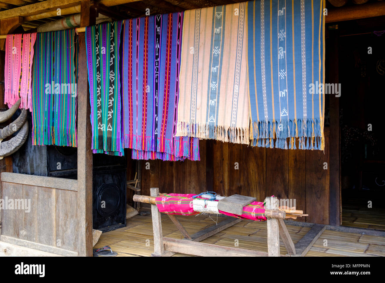 Traditional 'ikat' shawls and weaving loom at house entrance in Luba, hamlet (just outside Bena), Ngada District, Island of Flores, Indonesia. - Stock Image