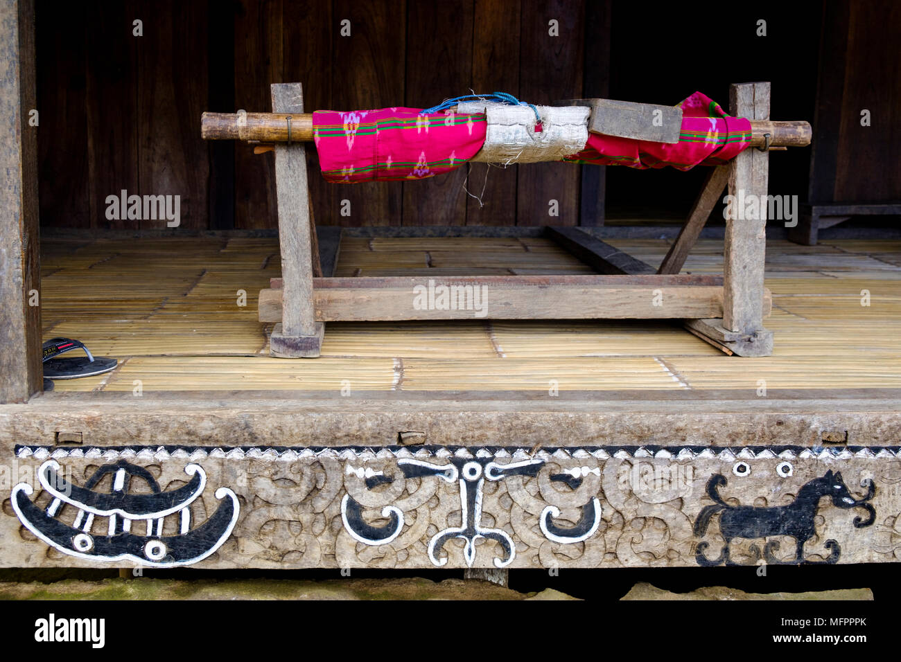 Loom and wood carved and painted decorations at entrance of traditional house, Luba, Ngada District, Island of Flores, Indonesia. - Stock Image