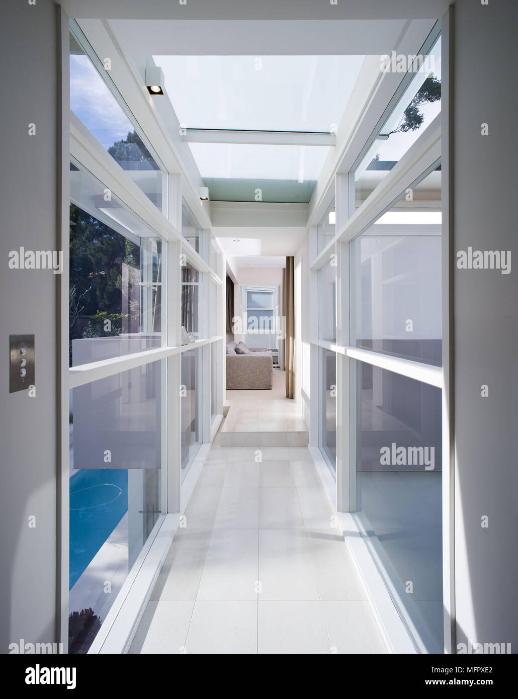 View along hallway of modern house with glass walls and roof