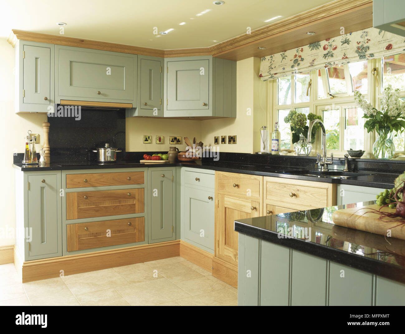 Country style kitchen with green fitted units