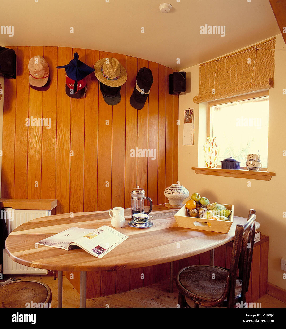 Collection Of Hats On Curved Wood Lined Wall In Country Kitchen