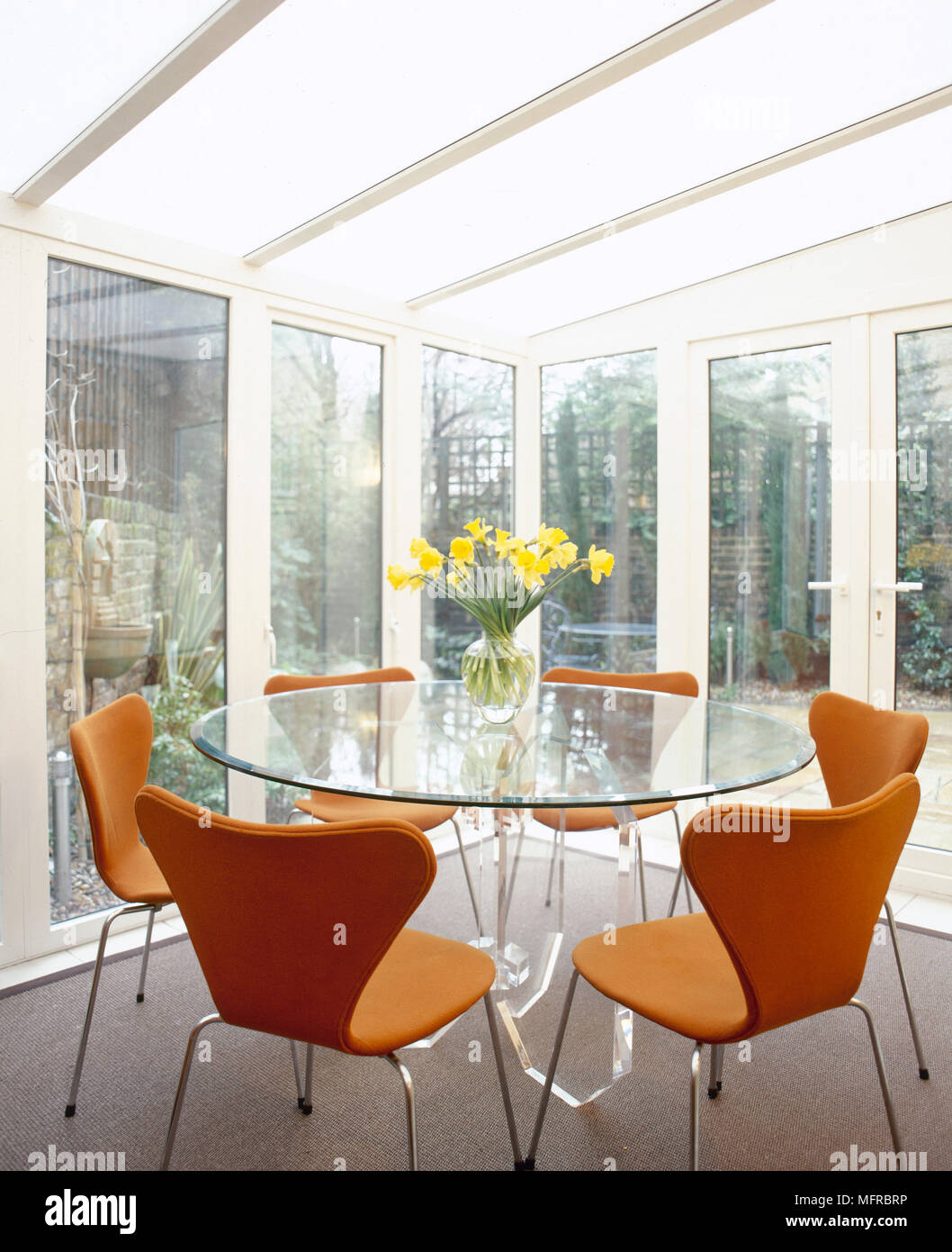 Modern Conservatory Dining Area With Glass Walls And Roof, Round Glass Table,  And Butterfly Back Chairs.