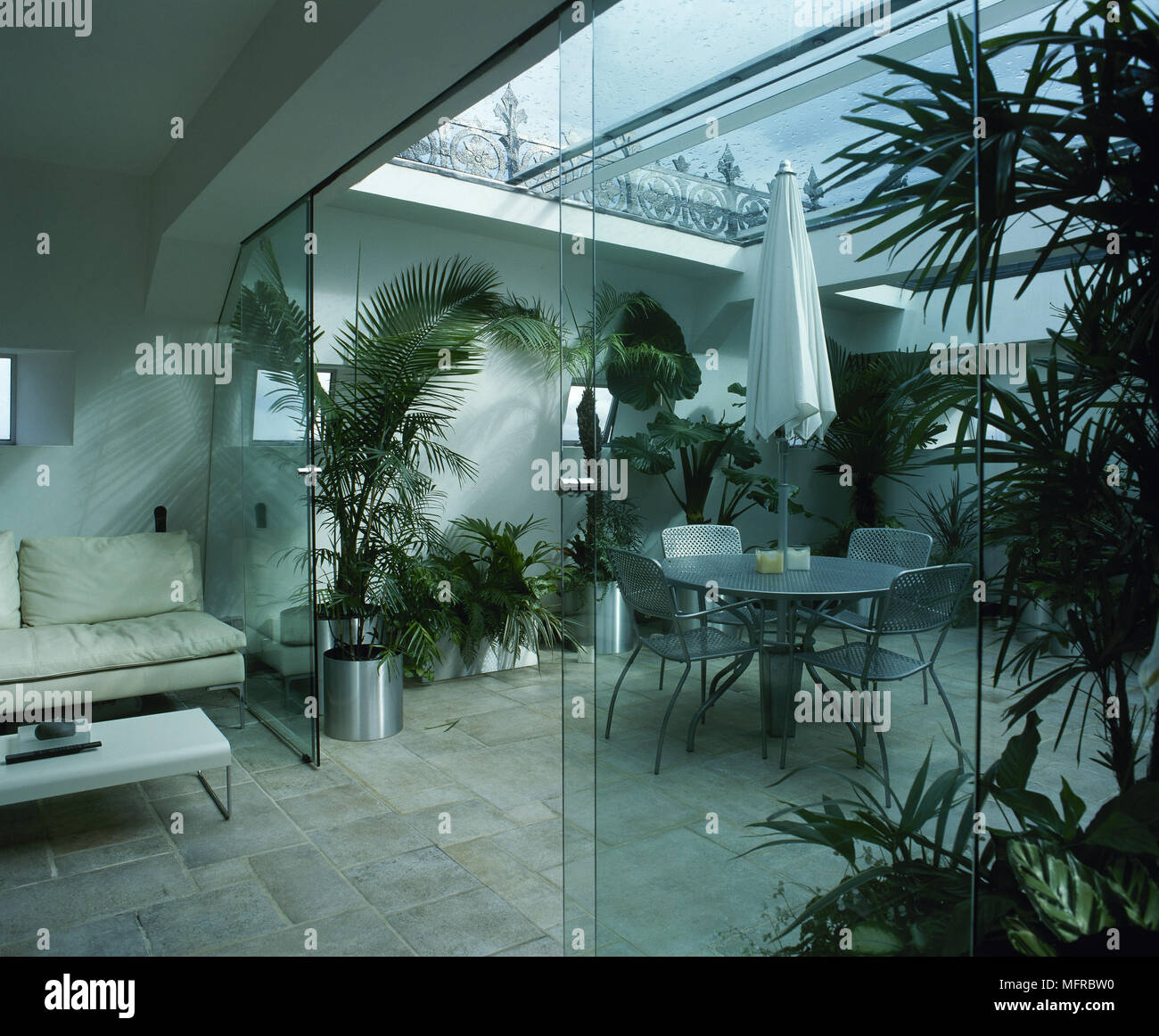 Conservatory With Sliding Glass Doors, Tile Floor, Glass Roof, Metal Dining  Table And Chairs.