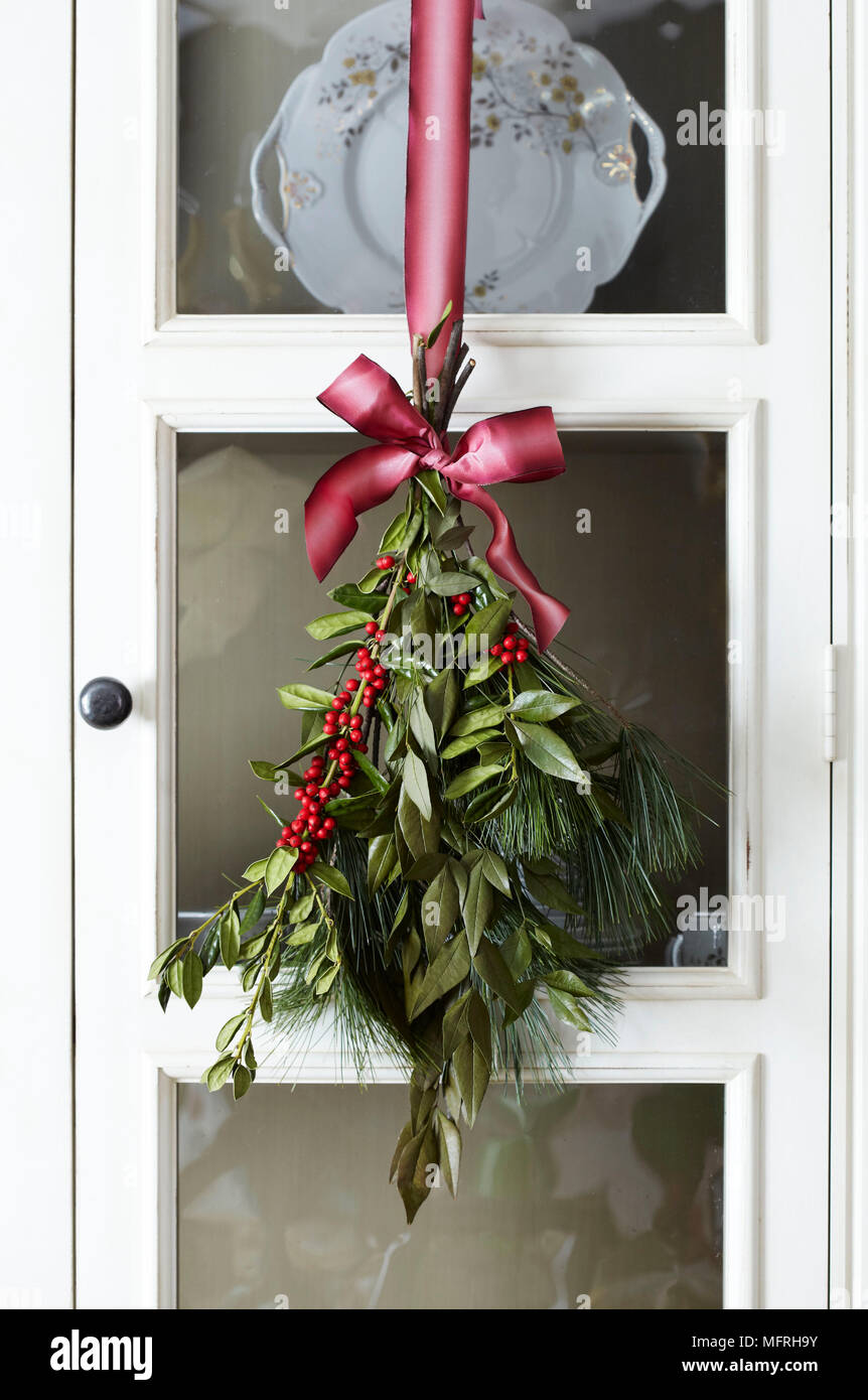 Christmas Leaves Hanging From Pink Ribbon In Front Of Glass Door Of