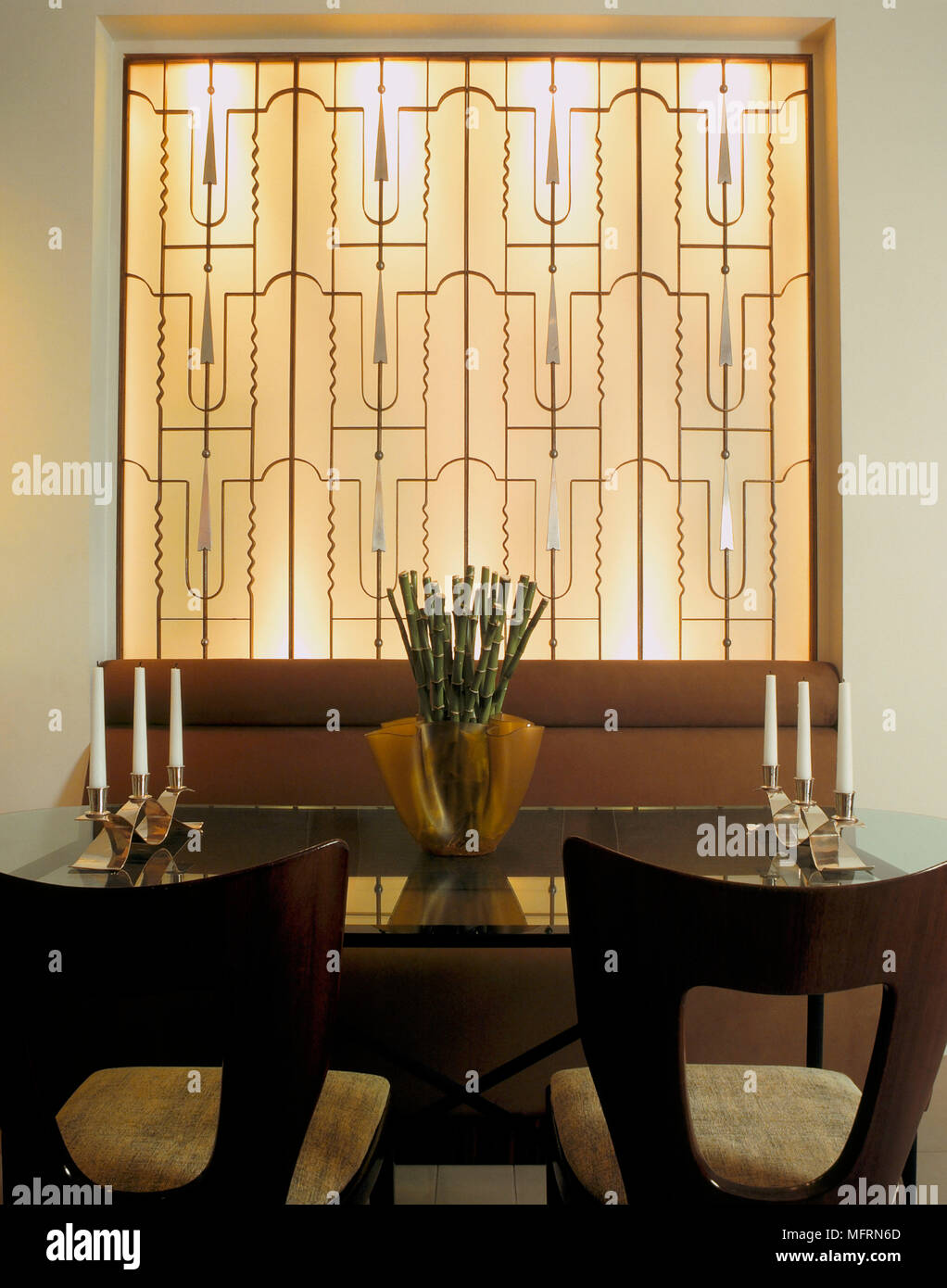 A detail of a modern dining room with glass table chairs banquette ...