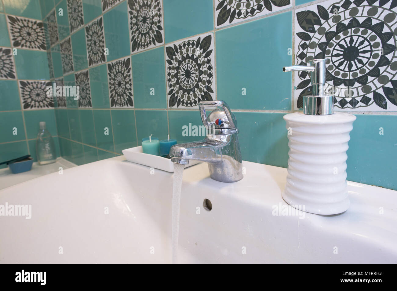 Porcelain wash basin with soap holder and decorative tiled wall ...