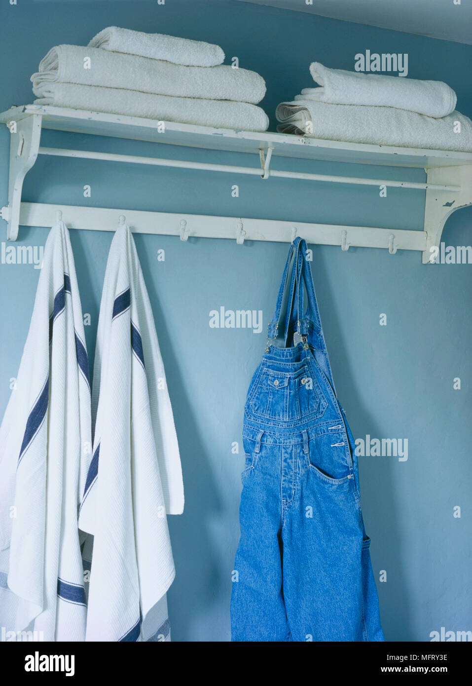 A detail of a blue country bathroom painted shelf with peg board ...