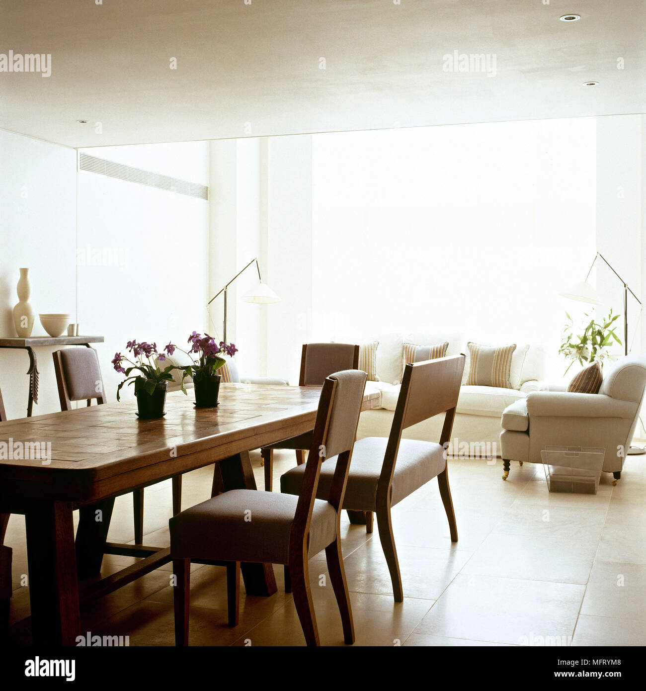Modern open plan neutral sitting room dining area wood table upholstered chairs sofas interiors rooms open plan contemporary living spaces light airy