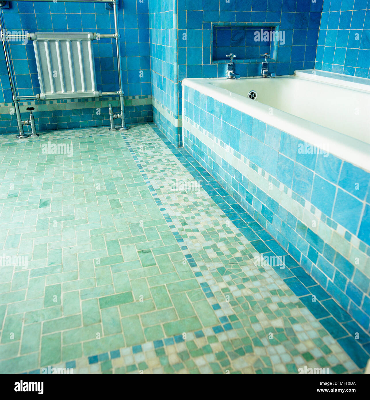 Radiator next to bathtub in blue tiled bathroom Stock Photo ...