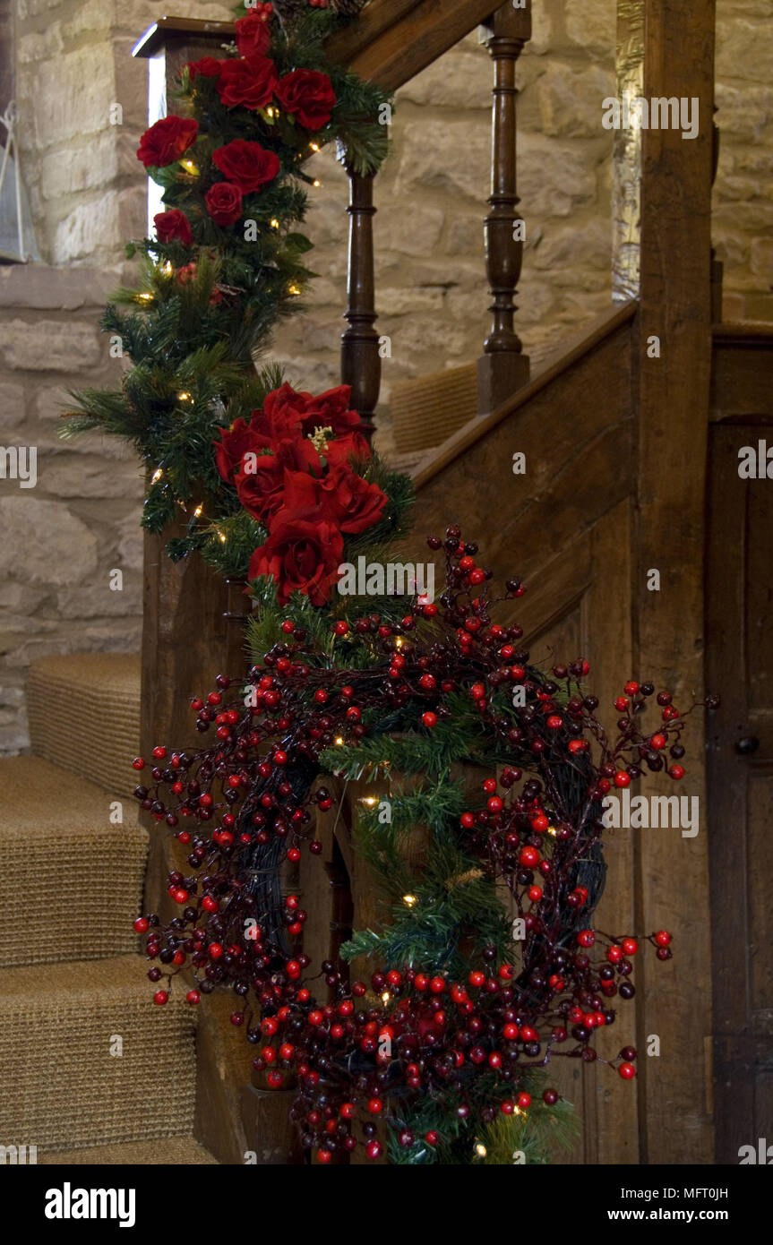 christmas garland of red flowers and foliage with wreath of berries on staircase banister - Banister Christmas Garland Decor