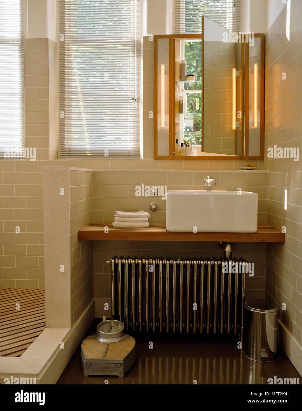 Square washbasin on wooden shelf above radiator next to shower area ...