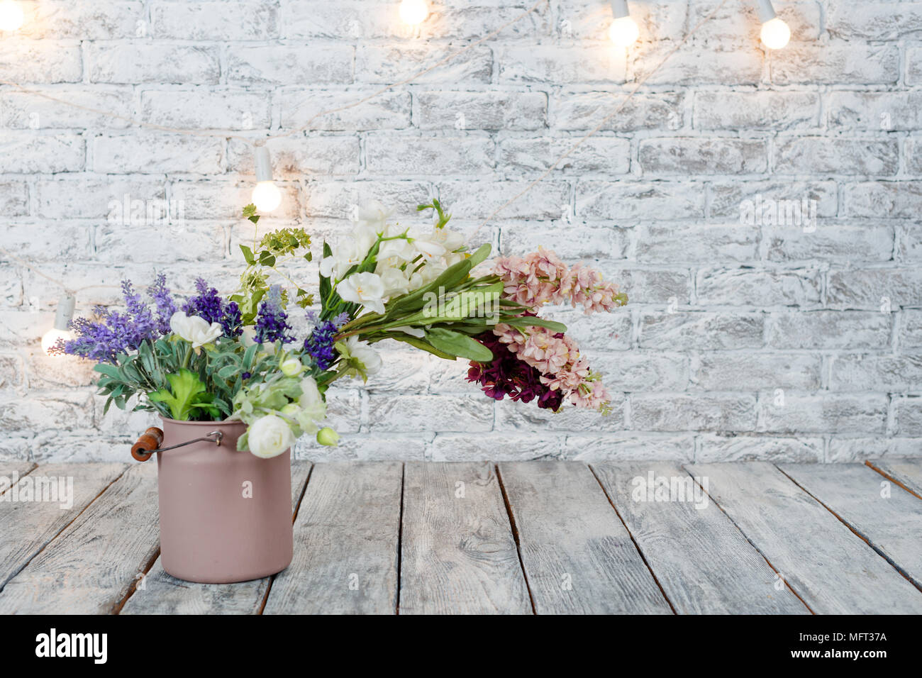 Flowers With Light Bulbs On White Brick Background With Wooden Floor