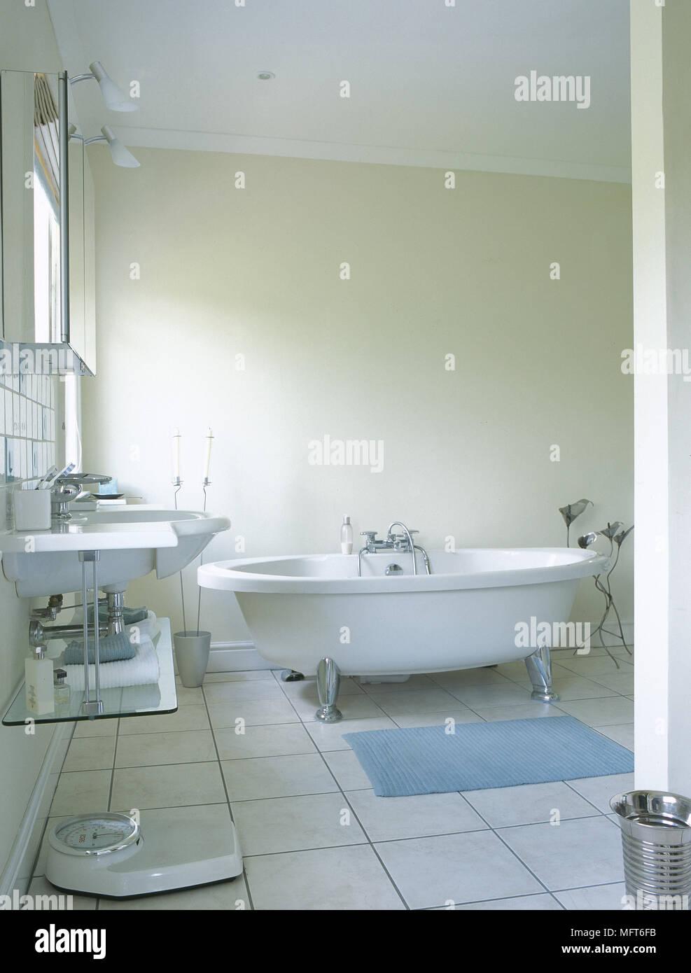 Modern bathroom with freestanding bathtub, sink with glass shelf ...