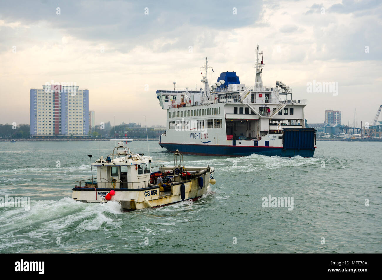 a-fishing-trawler-follows-a-wight-link-car-ferry-out-of-portsmouth-harbour-in-the-uk-MFT70A.jpg