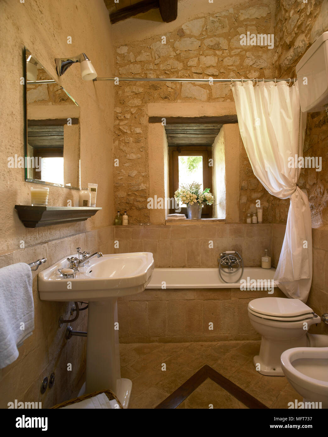 A country bathroom with exposed rustic stone walls, bath, pedestal ...