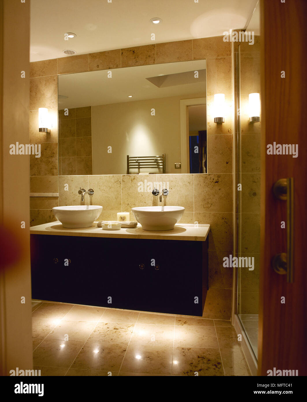 Modern, tiled bathroom with double sinks, large mirror, and lit wall ...