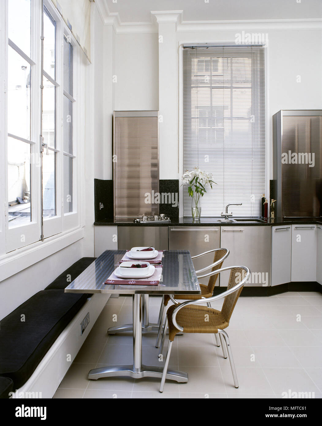 Modern eat in kitchen with stainless steel cabinets dining table with banquette seating tile floor and tall windows