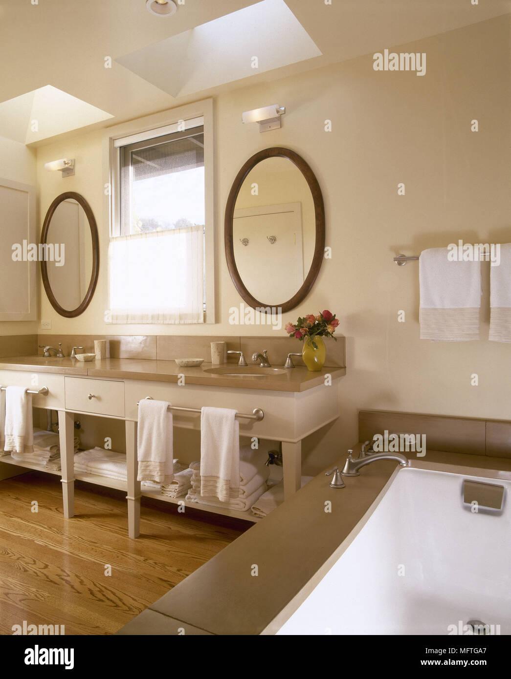 Modern neutral bathroom twin washbasins set on cupboard unit bath ...