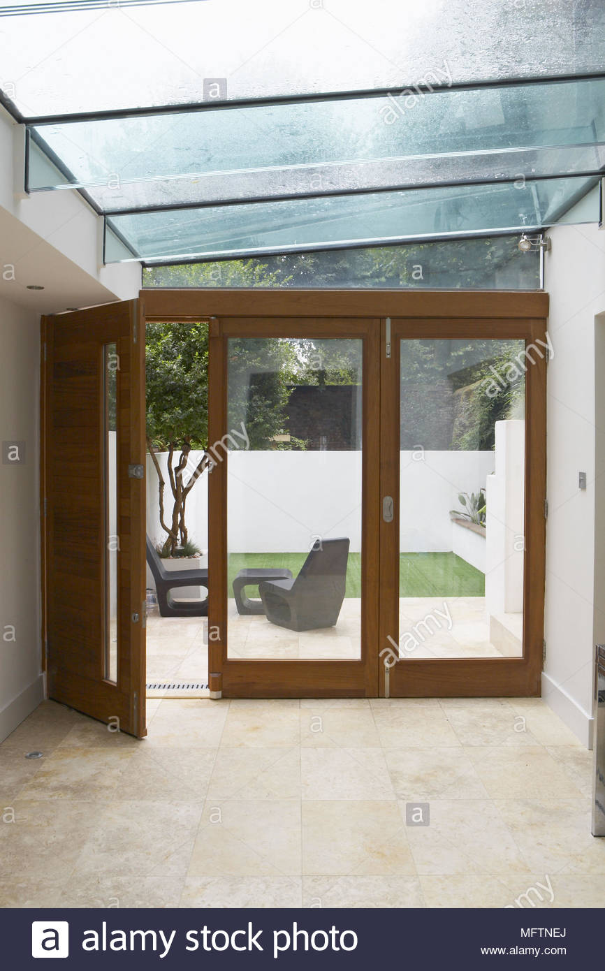 Hallway With Glass Roof And Open French Doors To Modern Courtyard Garden