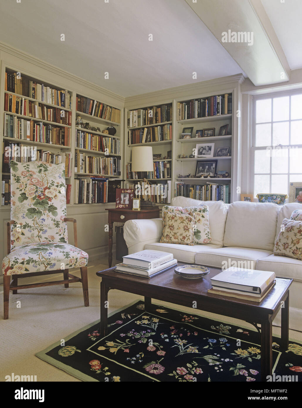 A Traditional Sitting Room With A Corner Bookshelf And A Small Coffee Table  With Seating Upholstered With A Floral Pattern.