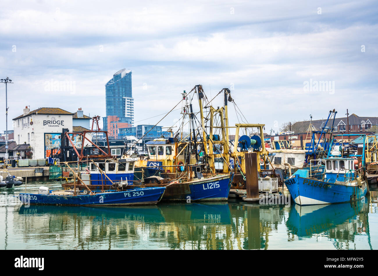 fishing-boats-moored-in-portsmouth-harbout-in-the-background-is-the-lipstick-tower-at-gunwharf-quays-MFW2Y5.jpg