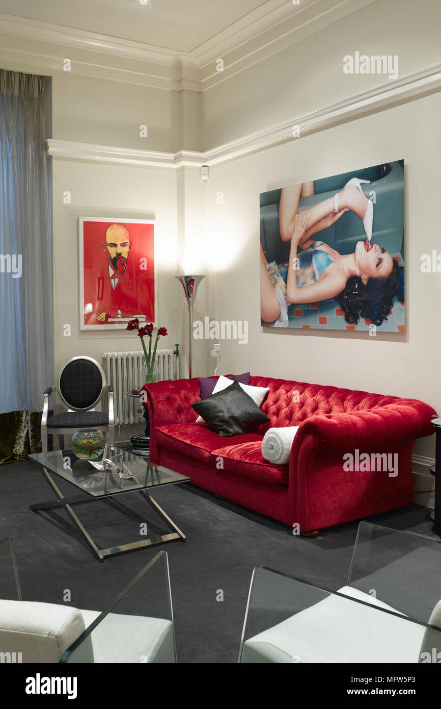 A modern sitting room with a red velvet sofa surrounded by two large pop art poster prints and in front of a glass coffee table