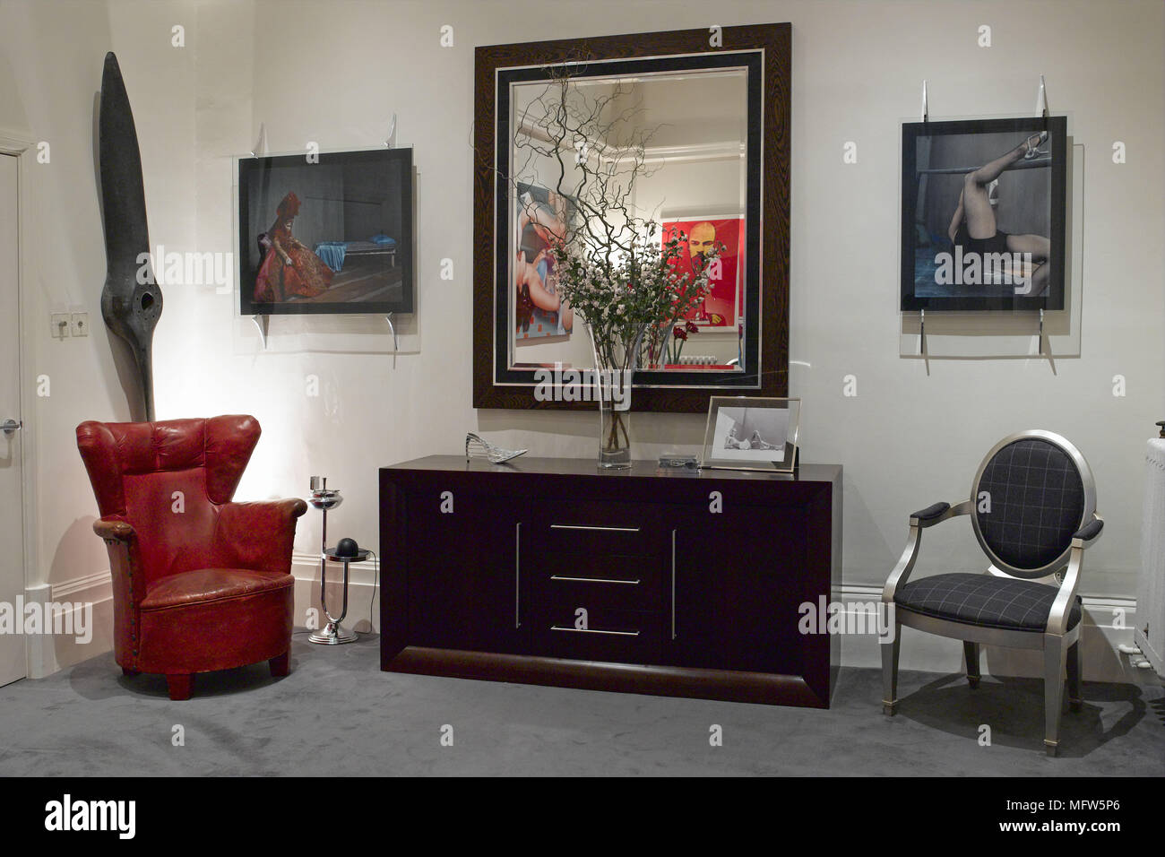 A modern sitting room with an eclectic selection of furniture and paintings including a wooden propeller mounted on the wall next to the door. & A modern sitting room with an eclectic selection of furniture and ...