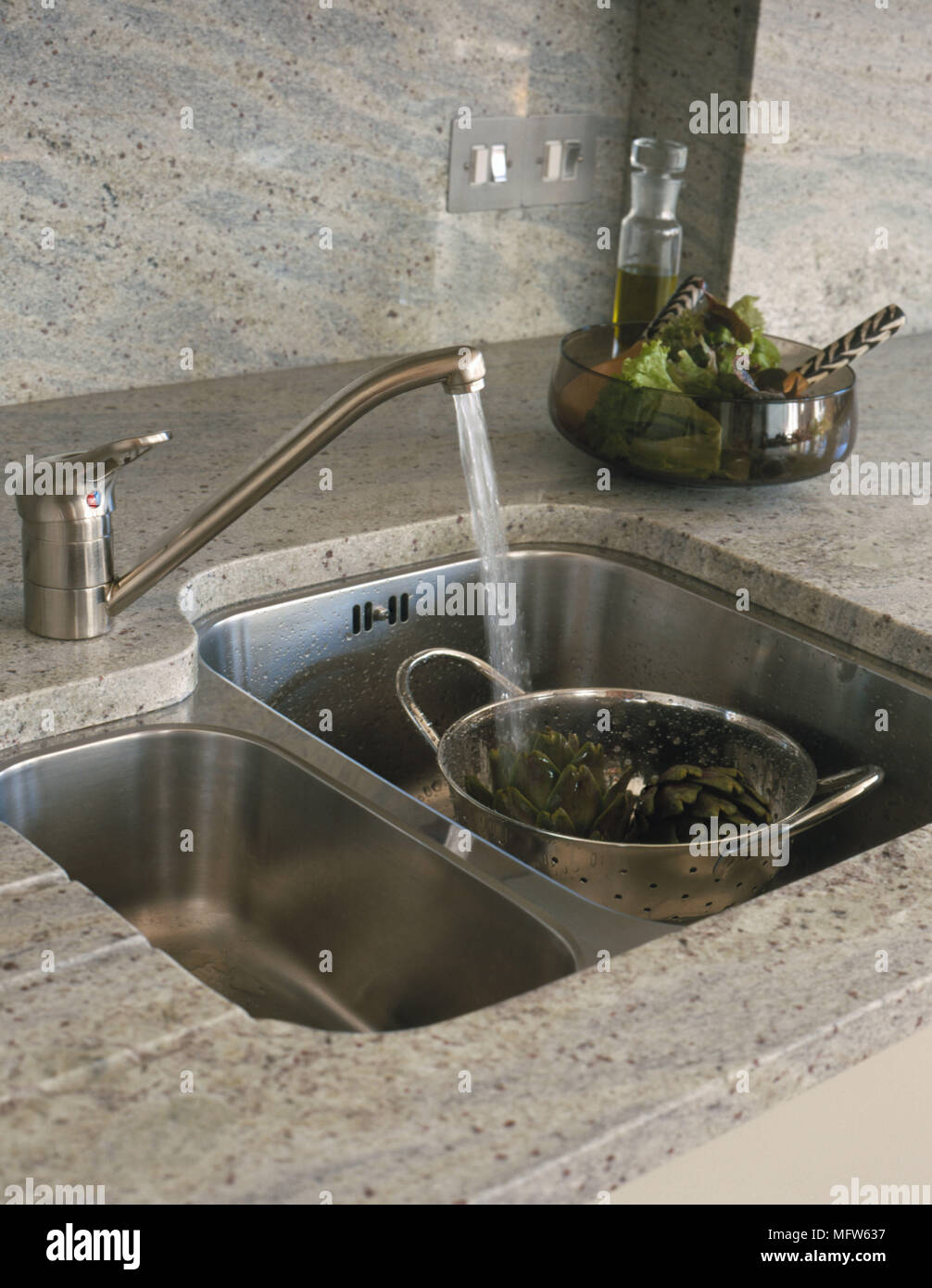 Details Of A Modern Stainless Steel Kitchen Sink With A Colander Surrounded  By A Polished Stone Work Surface.