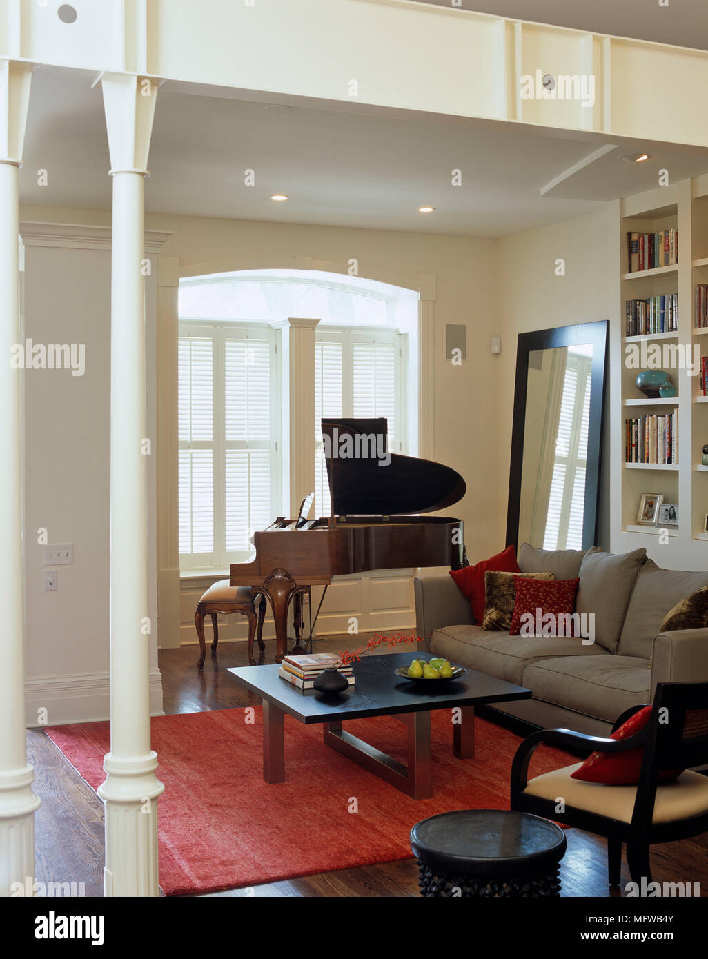 Piano in front of window next to sofa and coffee table in ...