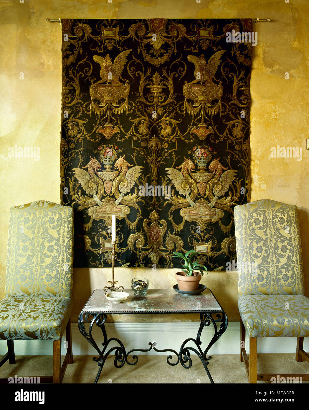 A Detail Of A Traditional Sitting Room With Yellow Walls, Tapestry Wall  Hanging, Gold Upholstered Chairs, Iron Table, Marble Top,