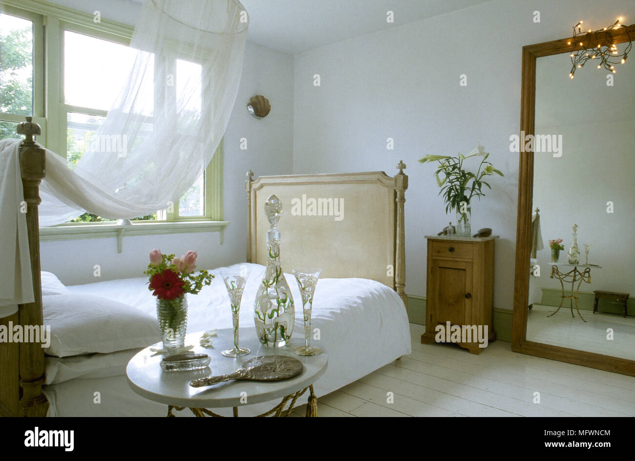 Romantic Bedroom With Sheer Canopy Over A Double Bed, Large Mirror, Bedside  Table, And A Sunny Window.