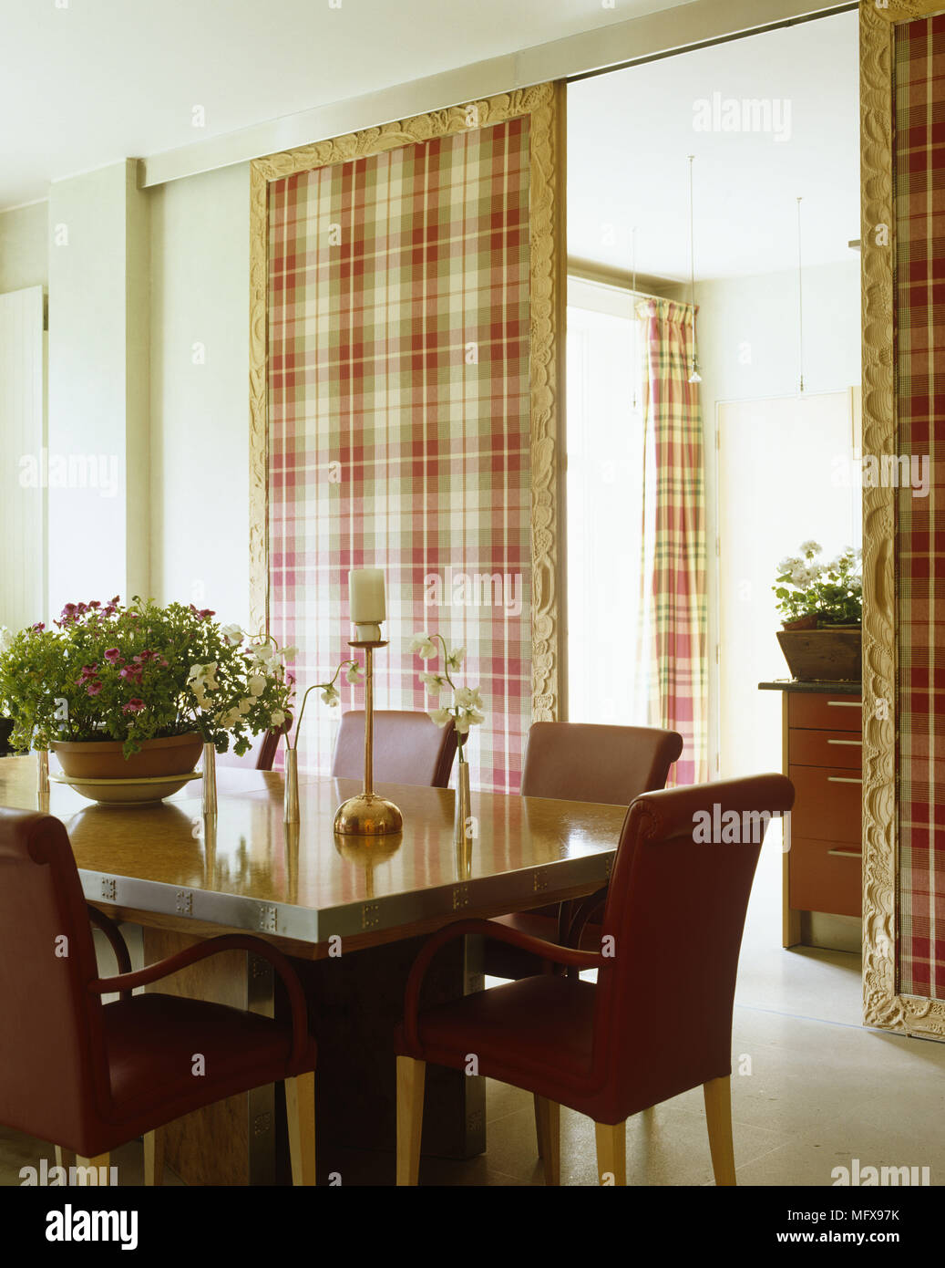 Houseplant On Dining Table And Upholstered Chairs In Front Of Sliding Doors  Covered In Plaid Fabric