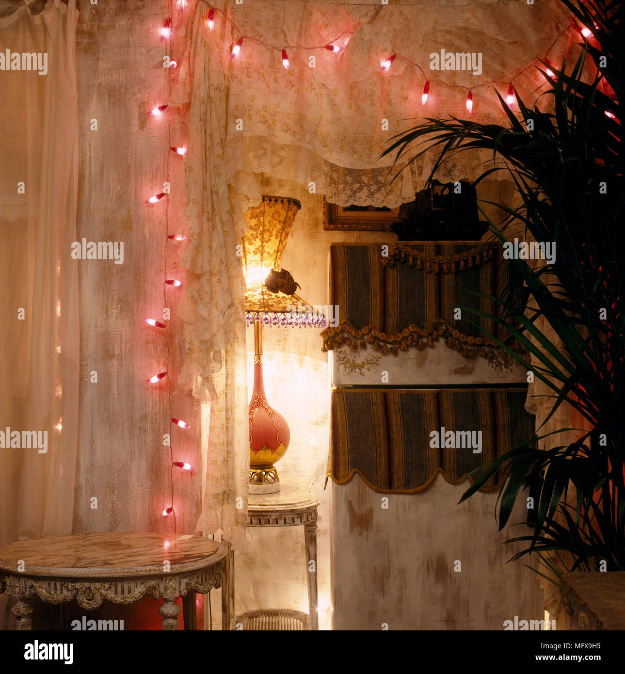 A Detail Of A Romantic Bedroom With Lit Fairy Lights Draped Around Lace  Curtains, Lit Lamp Giving A Subtle, Low Light Ambient
