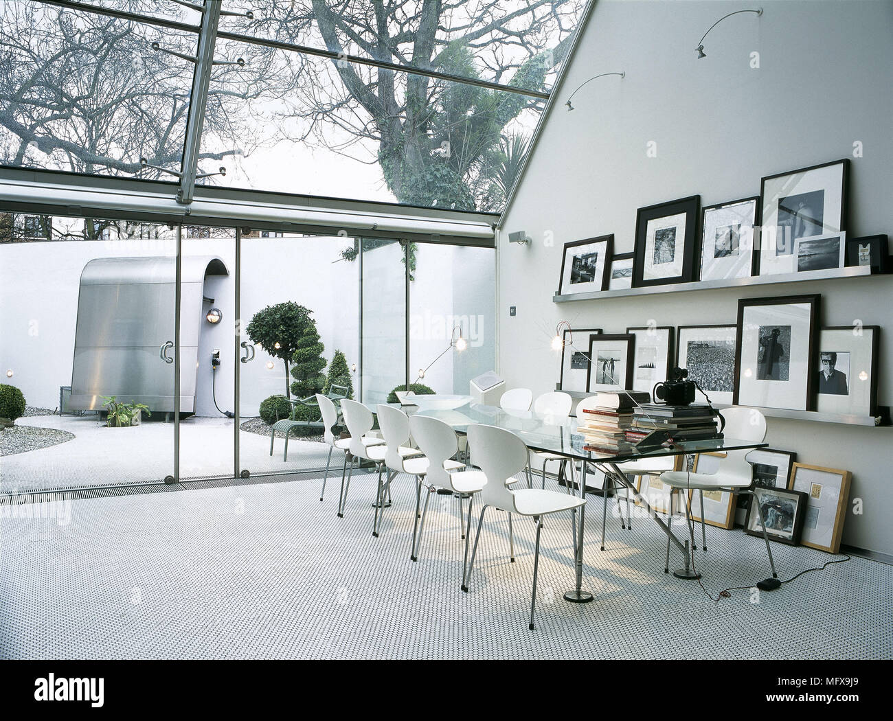 Dining Room With Sloping Glass Roof And Long Glass Table.